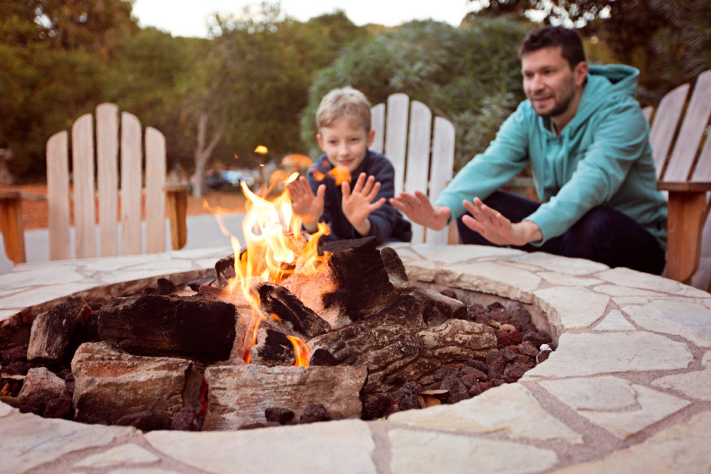 view of firepit and happy smiling family of two, father and son,.