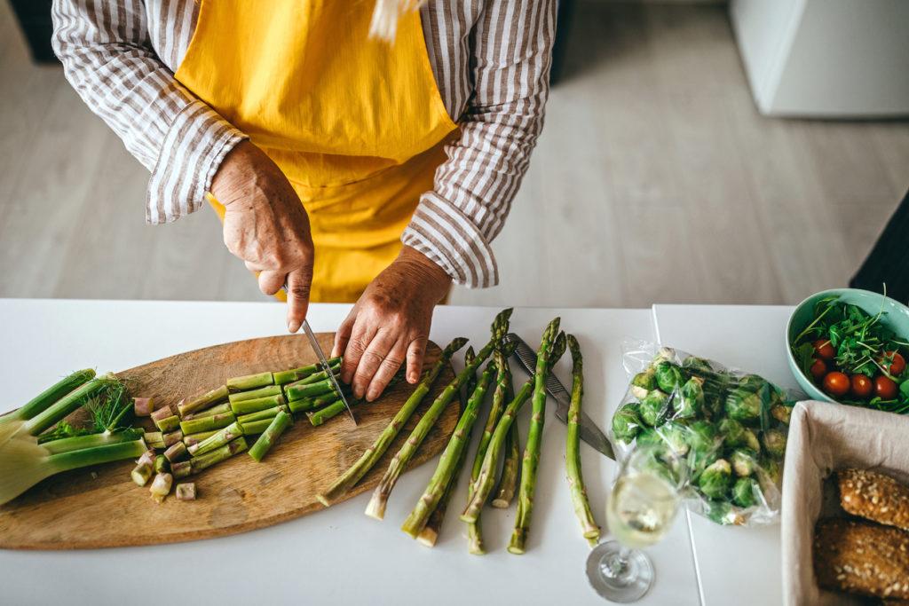 Senior woman cutting vegetable in kitchen