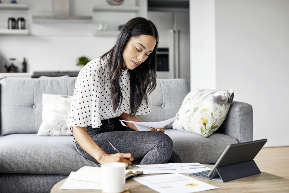 Young woman analyzing bills while writing in notebook.