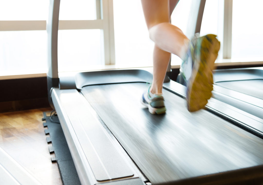 Unrecognizable woman running on treadmills