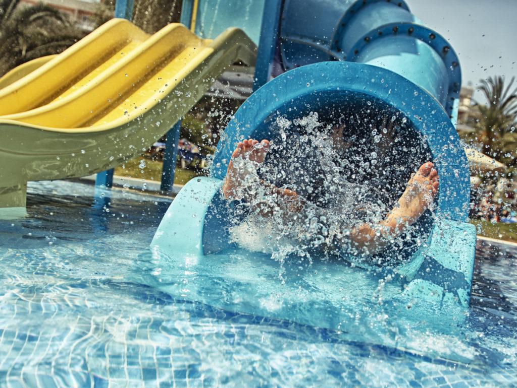 Little girl sliding down waterpark slide