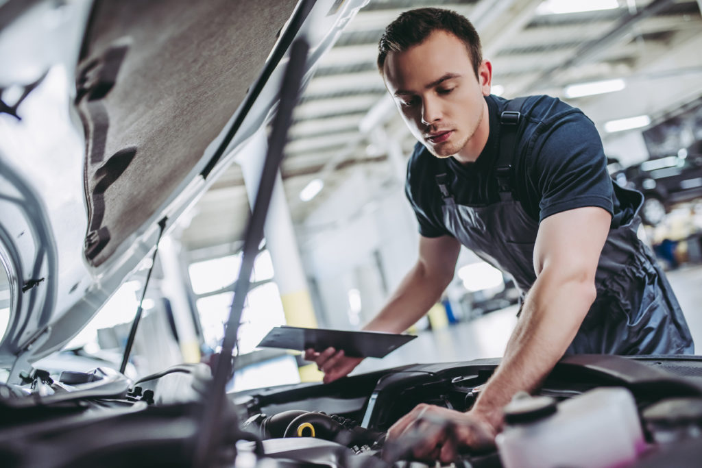 mechanic in uniform is examining the car while working in auto service. Car repair and maintenance.