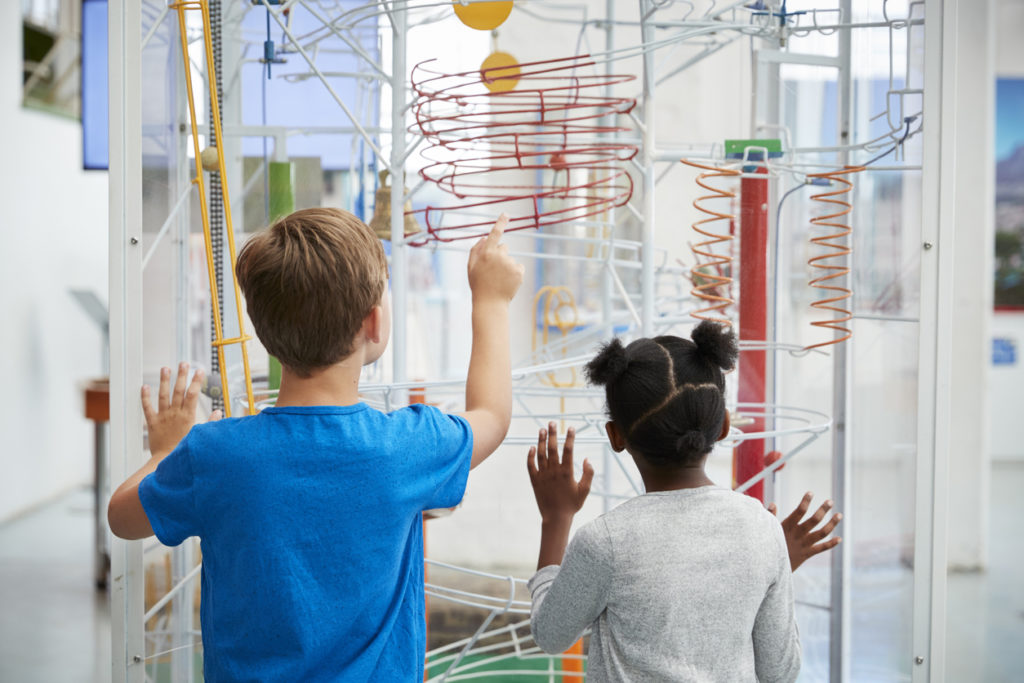 Two kids looking at a science exhibit,